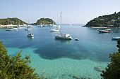A color landscape photo of sailing boats anchored in beautiful Lakka Harbour in Paxos Greece.The water is a stunning blue turquoise color. poster