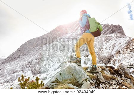 Woman hiker with backpack on top of mountain stopped on sunny mountain ledge to catch breath after long hike