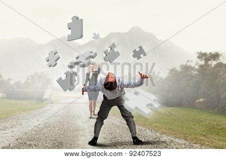 Businessman bent over and evading from flying puzzle element