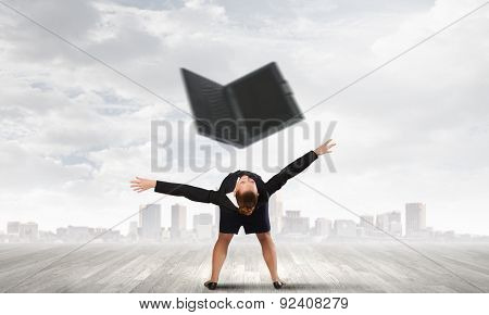 Young businesswoman evading back from flying laptop