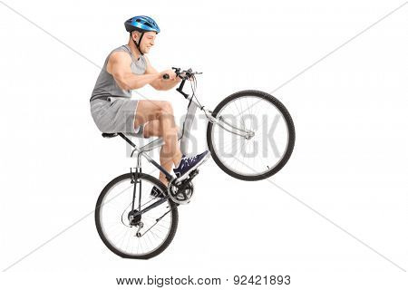 Studio shot of a joyful young biker doing a wheelie with his bicycle isolated on white background