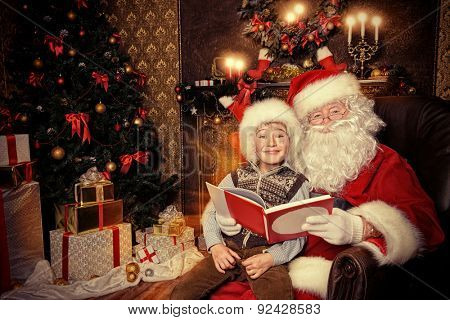 Santa Claus and happy boy sitting in Christmas room and reading a book. Christmas home décor.