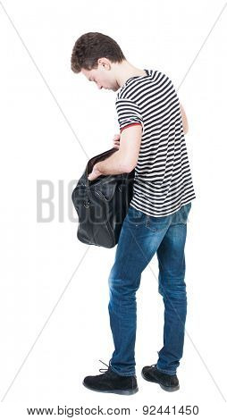 Back view of man in jeans with bag. Standing young guy.  The guy in the striped shirt with hands on hips standing. Man stands and delves into the bag.