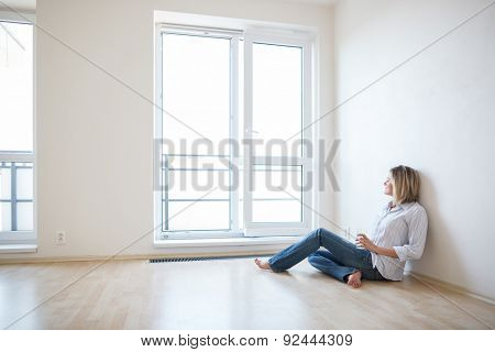 Just moved in: beautiful young woman finally sitting down and relaxing -  having a drink in her brand new modern apartment