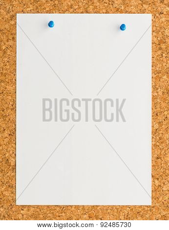 White Paper Note Sheet With Blue Push Pin On Cork Board