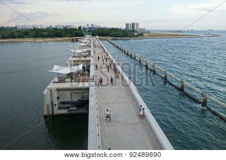 People Jog And Cycle On The Bridge Of Marina Barrage, Singapore