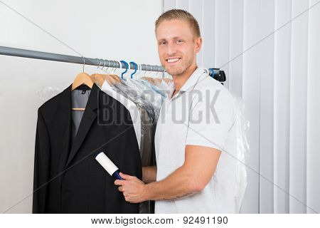 Man With Lint Roller In Clothes Store
