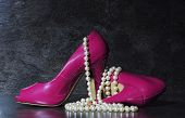 Glamorous pair of ladies pink high heels with long strand of white pearls against a dramatic black slate background still life. poster