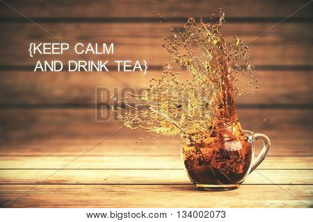 Keep calm and drink tea concept with splashing cup of tea on dark wooden background. 3D Rendering