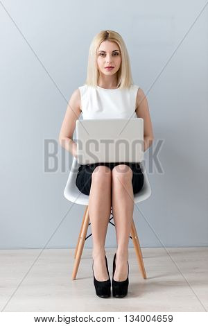 Full length portrait of attractive young businesswoman working on a laptop. She is sitting on chair and holding notebook on knees. The lady is looking at camera with confidence