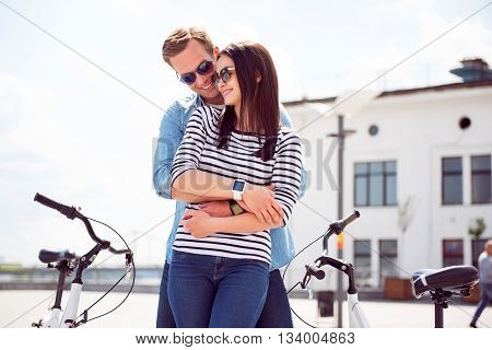 Nice meeting. Contended young man hugging back a pretty young woman with sunglasses while standing near bikes