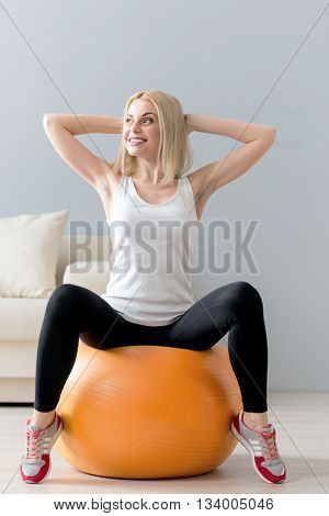 Attractive young woman is sitting on fitness ball and doing exercise. She is raising arms behind her head. The lady is looking aside and laughing