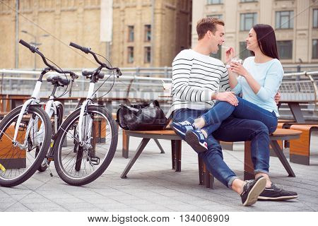 Having a rest together. Beautiful young woman spoon feeding ice cream to a handsome young man while sitting at the table