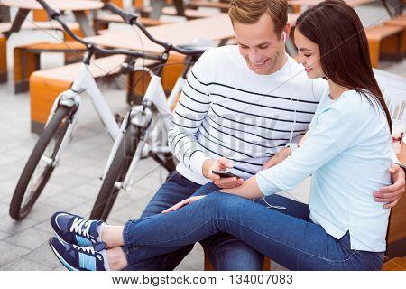 Good track. Contended young woman and relaxed young man sitting and listening to music on the smartphone after riding