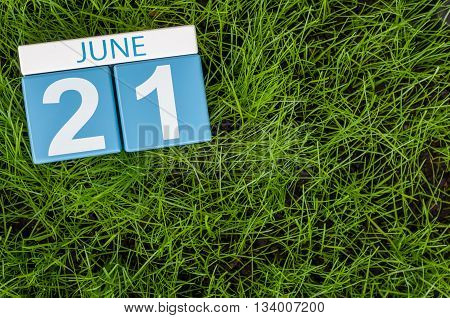 June 21st. Image of june 21 wooden color calendar on greengrass lawn background. Summer day, empty space for text.