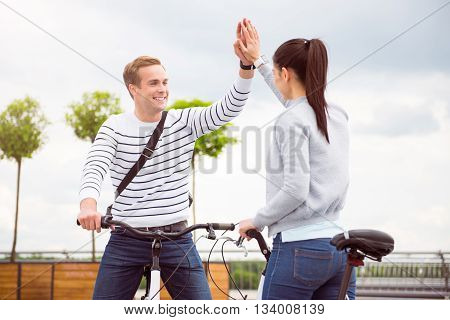 Give me five. Contended young man giving five to lovely young woman while sitting on the bikes