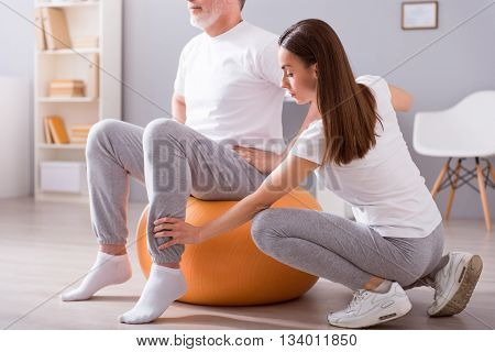 Rehabilitation. Cropped picture of male patient sitting on gym ball with concentrated female physiotherapist performing some rehab exercises