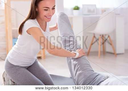 Chiropractor. Male patient lying down on a mat and female glad and smiling physiotherapist performing some stretch exercises on mans leg