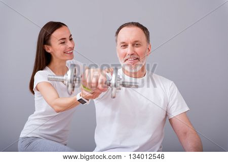 Exercising together. Happy male patient with dumbbells during physical therapy praxis and positive female physiotherapist helping him