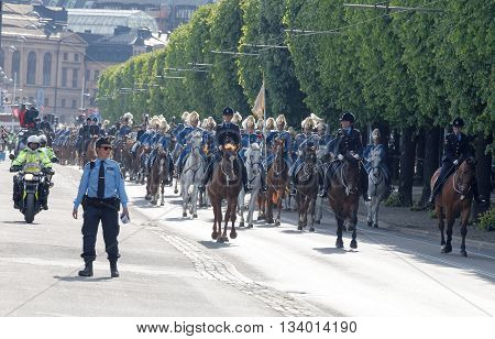 STOCKHOLM - JUN 06 2016: The Royal guards on the horse back and the police protecting the swedish royal family on their way to celebrate the swedish national day