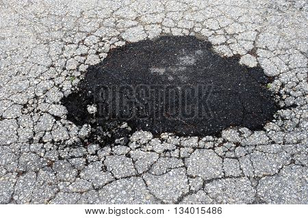 cracked asphalt road surface and repair patch