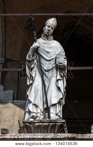 14th century statue portraying a bishop on the upper loggia of the Cremona Cathedral