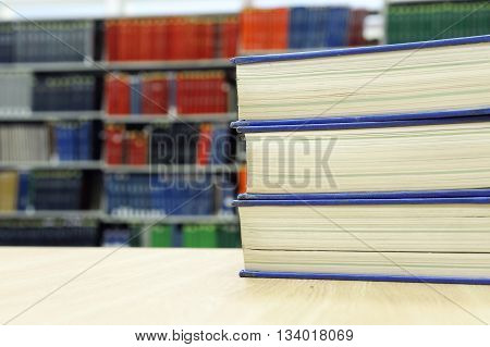 stacking books on the table against bookshelf in library
