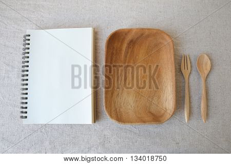 Empty wooden plate with fork spoon and white notebook mock up