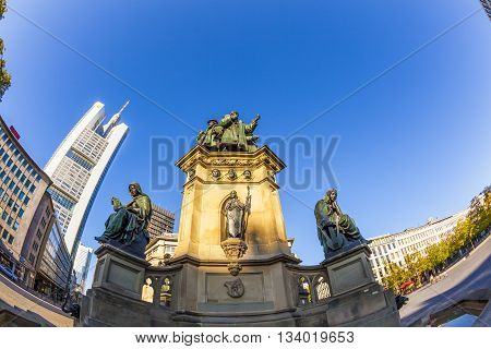 FRANKFURT, GERMANY - JUNE 9, 2012: statue of Johannes Gutenberg inventor of book printing with skyscrapers Frankfurt Germany