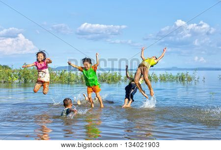 Dong Nai, Vietnam - November 15th, 2015: Children bathing in lake afternoon with dancing movements, flying directly into water as exciting games of childhood innocence rural areas in Dong Nai, Vietnam
