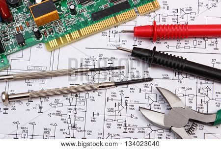 Printed circuit board with electrical components precision tools and cable of multimeter on construction drawing of electronics drawings and tools for engineer jobs