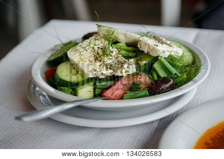 Greek salad with feta cheese, cucumber, tomatoes, olives, dill, seasoning and olive oil. Made in local taverna at Corfu.