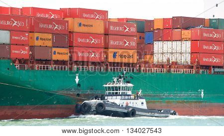 Oakland CA - June 09 2016: Tugboat Z-FOUR off the port side of cargo ship SEASPAN HAMBURG assisting the vessel to maneuver into the Port of Oakland.