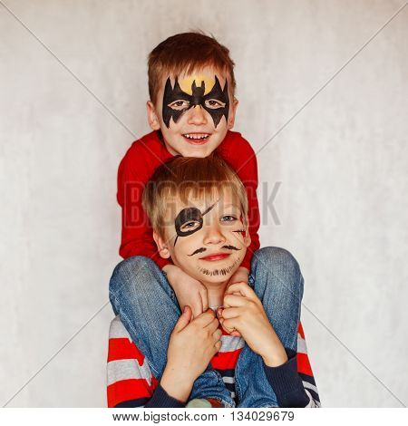 Two boys with face art of a hero and pirate. Having their faces painted on birthday party.