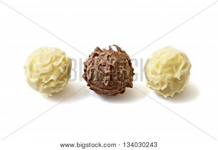 Closeup of white and dark chocolate candies on white background.