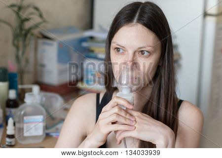 Young Woman Turning On Respiratory Inhaler
