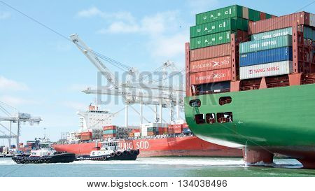 Oakland CA - June 09 2016: Tugboats VETERAN and SANDRA HUGH at the stern of cargo ship CSCL WINTER assisting the vessel to maneuver into the Port of Oakland.
