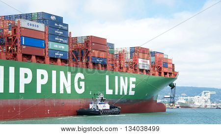 Oakland CA - June 09 2016: Tugboat REVOLUTION off the starboard side of Cargo Ship CSCL WINTER assisting the vessel to maneuver into the Port of Oakland.