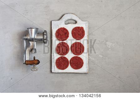 Fresh beef patties for burgers with vintage meat grinder on a white surface top view