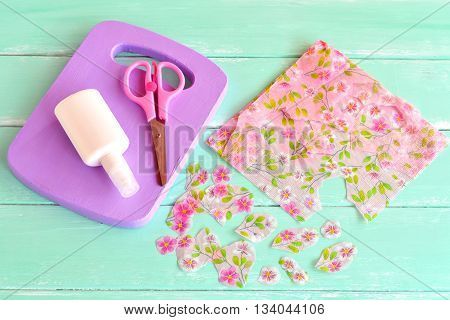 Painted wooden kitchen board. Wooden handmade chopping board kitchen decor. Paper napkin, cut floral fragments, scissors. Decoration items. Set for decoupage, recycled crafts