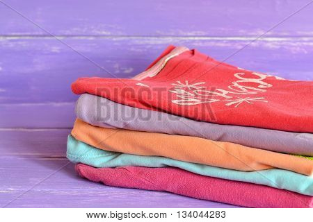 Stack of colorful clothes for baby girls on lilac wooden background. Collection of girls raglan cotton. Red, lilac, orange, pink, blue children clothes stacked in a pile. Close-up