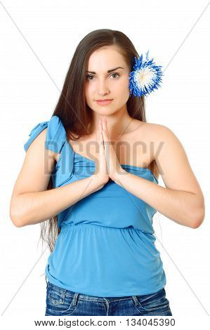 nice-looking attractive woman with flower in long dark hair in blue t-shirt stands folding arms on white background, isolated