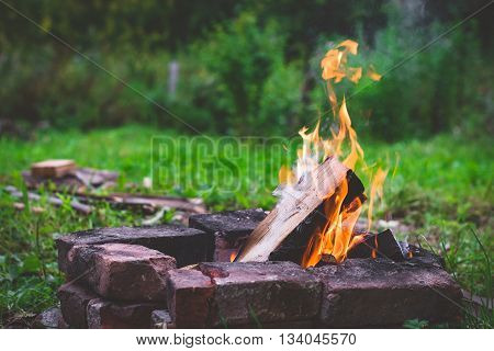 Camping at the summer: burning fire outside surrounded with bricks