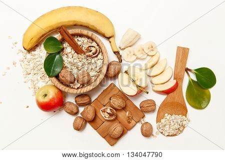 There are Banana,Apple,Orange with Walnuts in the Wooden Plate and Rolled Oats,Wooden Spoon,Trivet,with Green Leaves,Healthy Fresh Organic Food on the White Background,Top View
