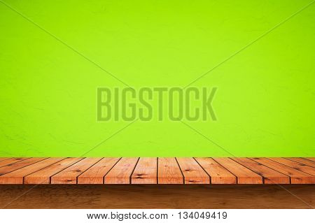 Empty wooden table with green wall background. For display or montage your products.