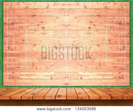Empty wooden table with football field wall background. For display or montage your products