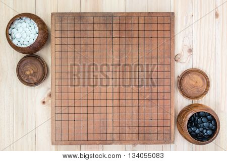top view two wooden bowls filled black and white stones with empty go game board on wooden table traditional chinese strategy board game sport hobby and recreation poster