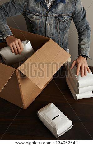 Bearded Brutal Man In Jeans Work Jacket Puts Blank Sealed Hermetic Packages Inside Big Carton Paper