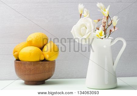 Wooden bowl with lemons and white flowers in jug.