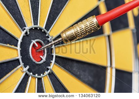 closeup red dart arrow hitting in target bullseye of dartboard business solutions and success concept